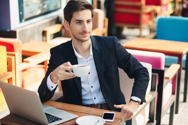 Young handsome man enjoy coffee working on laptop