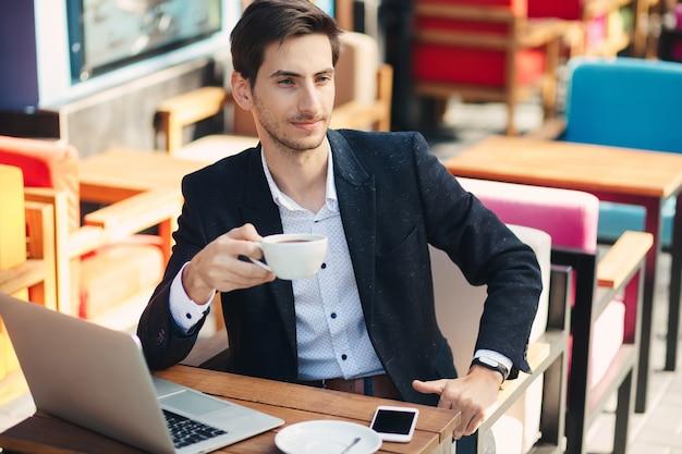 Молодой красавец наслаждаться кофе работает на ноутбуке