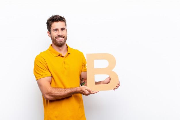 Молодой красивый мужчина взволнован, счастлив, радостен, держа букву b алфавита, чтобы сформировать слово или предложение.