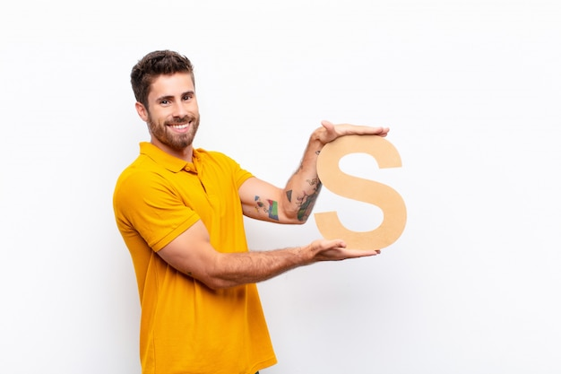 Молодой красавец возбужден, счастлив, радостен, держа букву s в алфавите, чтобы сформировать слово или предложение.