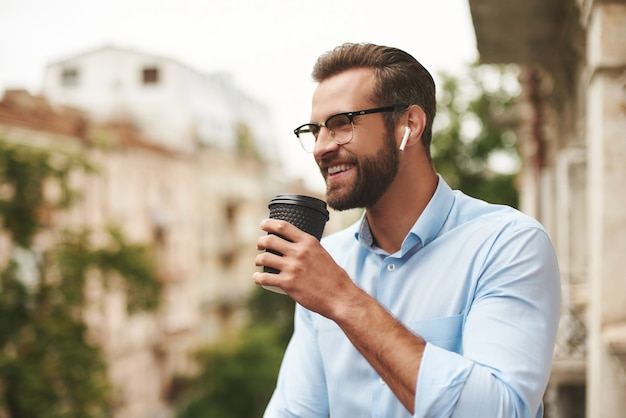 Young and handsome man in eyeglasses and headphones holding cup of coffee and talking with friend