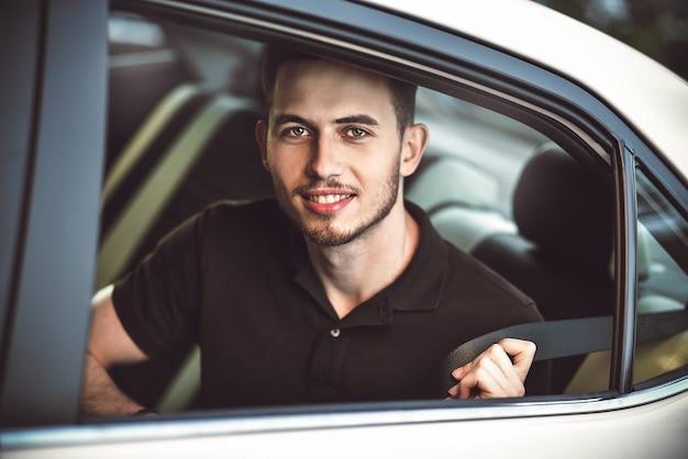 若いハンサムな男が車の後部座席に座ってシートベルトを締めます。