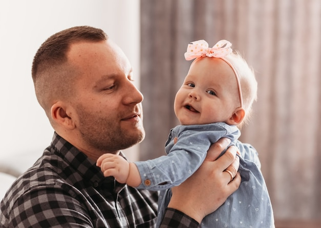 A young handsome man father holds a small daughter in his arms. infant girl and father smile