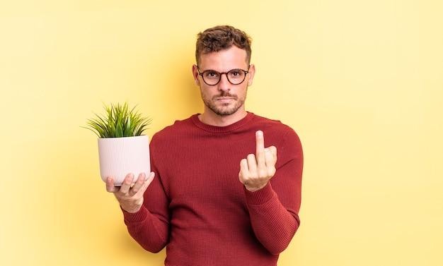 Молодой красивый мужчина чувствует себя злым, раздраженным, мятежным и агрессивным. концепция декоративного растения