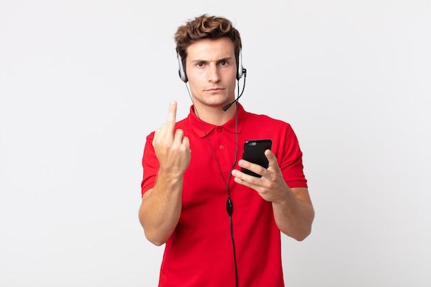 スマートフォンとヘッドセットで怒り、イライラ、反抗的、攻撃的な若いハンサムな男