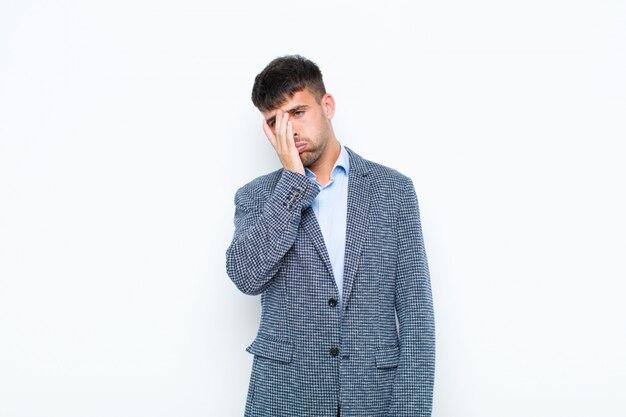 Молодой красавец чувствует скуку, разочарование и сонливость после утомительной, скучной и утомительной работы, прижав лицо рукой к белой стене