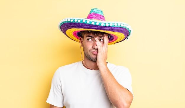 Молодой красавец чувствует себя скучающим, расстроенным и сонным после утомительного. концепция мексиканской шляпы