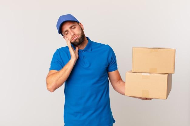 Молодой красавец чувствует себя скучающим, расстроенным и сонным после утомительного. концепция доставки пакетов