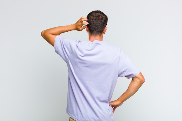 無知で混乱している若いハンサムな男、解決策を考えて、腰に手を、頭に他の人、背面図