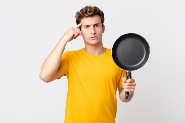 Молодой красивый мужчина смущен и озадачен, показывая, что вы сошли с ума, и держит сковороду