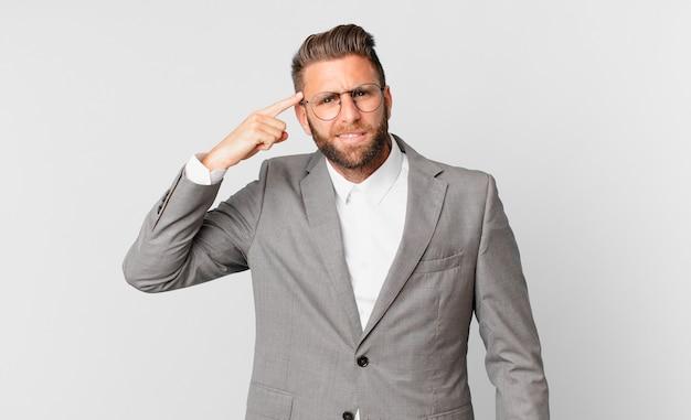 Молодой красивый мужчина смущен и озадачен, показывая, что вы сошли с ума. бизнес-концепция