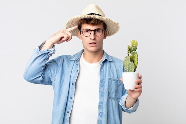 Молодой красивый мужчина смущен и озадачен, показывая, что вы сошли с ума. фермер держит декоративный кактус
