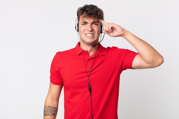 Молодой красивый мужчина смущен и озадачен, показывая, что вы сошли с ума. концепция телемаркетинга