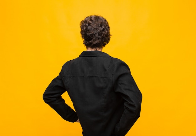 Young handsome man feeling confused or full or doubts and questions, wondering, with hands on hips, rear view against orange wall