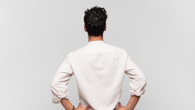 混乱したり、満腹になったり、疑問や質問を感じたり、疑問に思ったり、腰に手を当てて、背面図を感じている若いハンサムな男