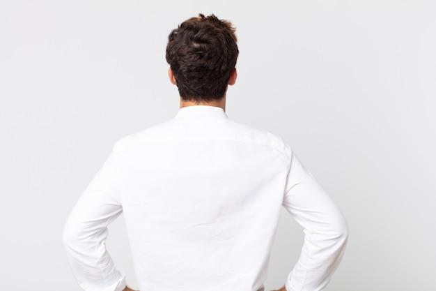 젊고 잘생긴 남자는 혼란스럽거나 가득 차거나 의심과 질문을 하고, 엉덩이에 손을 얹고, 후면을 봅니다.