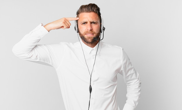 Young handsome man feeling confused and puzzled, showing you are insane. telemarketing concept
