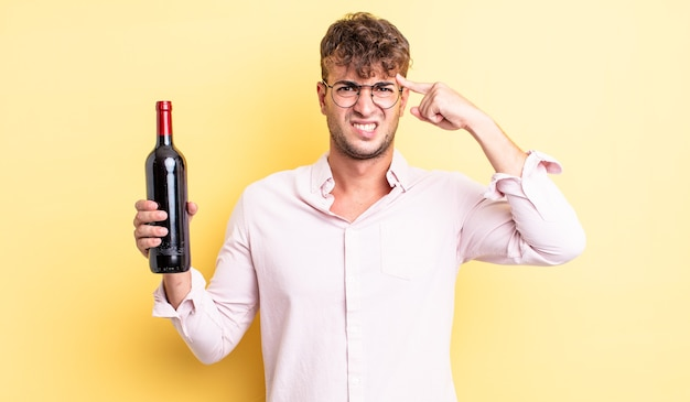 Young handsome man feeling confused and puzzled, showing you are insane. wine bottle concept