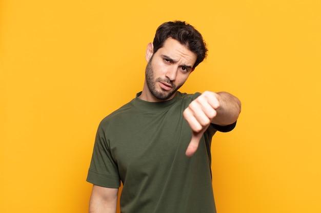Молодой красавец чувствует себя сердитым, злым, раздраженным, разочарованным или недовольным, показывая большой палец вниз с серьезным взглядом
