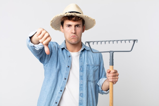 Young handsome man feeling cross,showing thumbs down. farmer concept