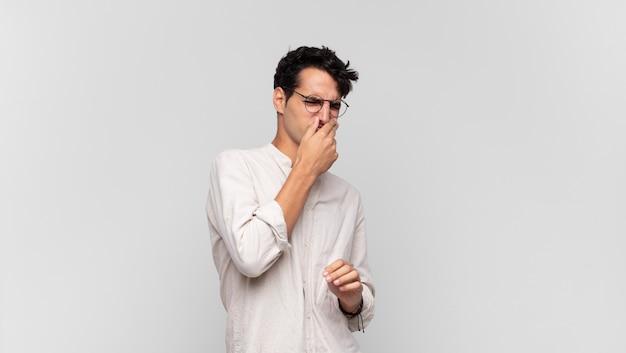 혐오감을 느끼는 젊은 잘 생긴 남자, 파울하고 불쾌한 악취를 피하기 위해 코를 잡고