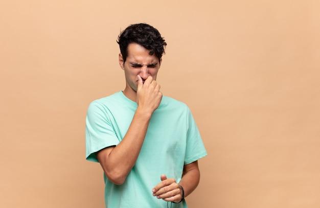 嫌悪感と不快な悪臭を嗅ぐのを避けるために鼻を保持している若いハンサムな男