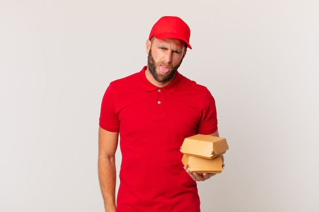 Young handsome man feeling disgusted and irritated and tongue out burger delivering concept