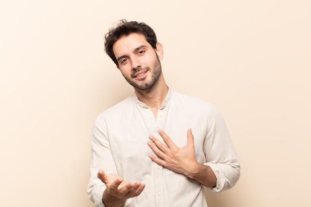 幸せで恋をしている若いハンサムな男は、片方の手が心の横に、もう片方の手が前に伸びて笑っている