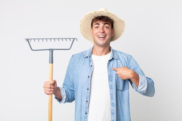 젊고 잘생긴 남자는 행복하고 흥분하여 자신을 가리키고 있습니다. 농부 개념
