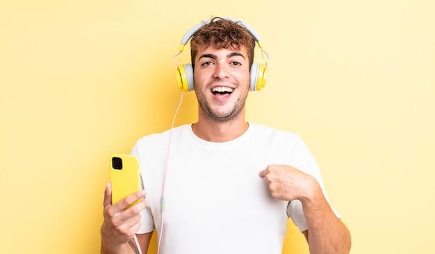 幸せを感じ、興奮して自分を指している若いハンサムな男。ヘッドフォンとスマートフォンのコンセプト
