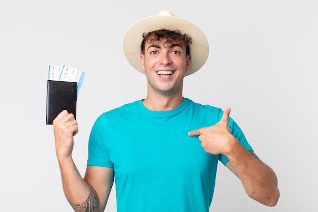 젊고 잘생긴 남자는 행복하고 흥분하여 자신을 가리키고 있습니다. 여권을 들고 있는 여행자