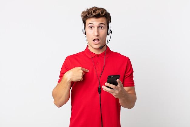 Молодой красавец чувствует себя счастливым и возбужденно указывая на себя со смартфоном и гарнитурой