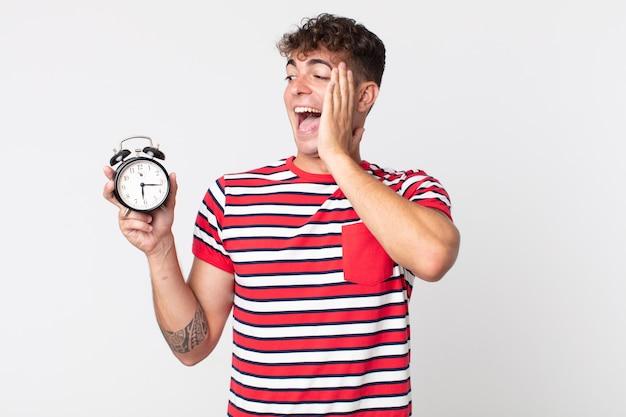 幸せ、興奮、驚きを感じ、目覚まし時計を持っている若いハンサムな男