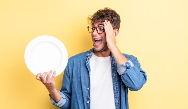 Молодой красивый мужчина чувствует себя счастливым, взволнованным и удивленным. концепция пустого блюда