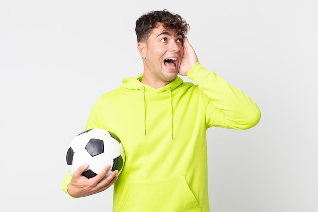 Young handsome man feeling happy, excited and surprised and holding a soccer ball