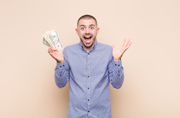 Young handsome man feeling happy, excited, surprised or shocked, smiling and astonished at something unbelievable with dollar banknotes