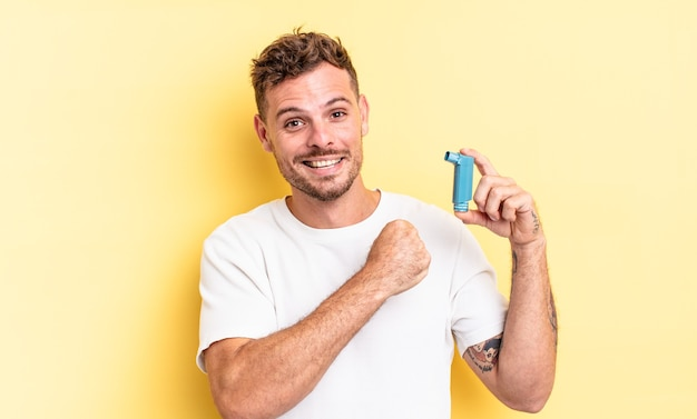 Young handsome man feeling happy and facing a challenge or celebrating. asthma concept