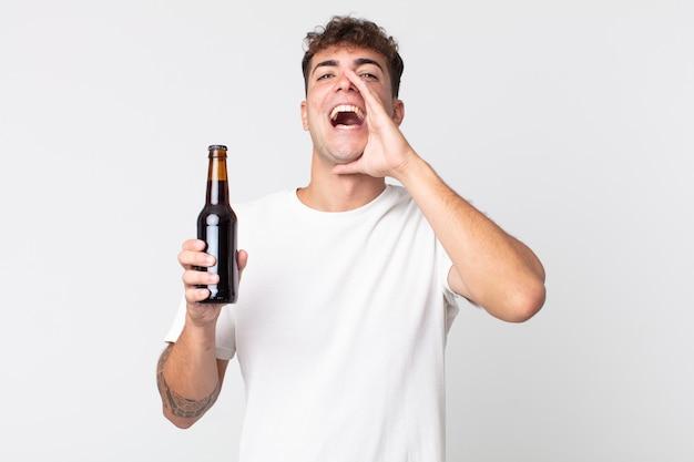 幸せを感じて、口の横に手で大きな叫びを与え、ビール瓶を持っている若いハンサムな男