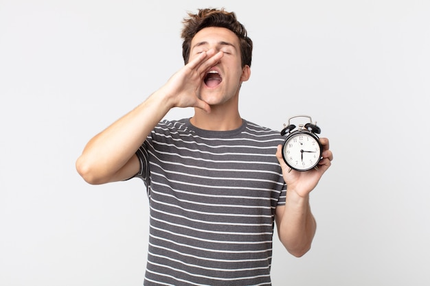 幸せを感じ、口の横に手で大きな叫びを与え、目覚まし時計を保持している若いハンサムな男
