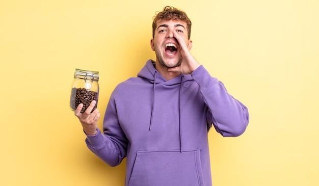 젊고 잘생긴 남자는 행복감을 느끼며 입 옆에 손을 대고 큰 소리로 외칩니다. 커피 콩 개념