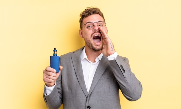 Young handsome man feeling happy,giving a big shout out with hands next to mouth. vaporizer concept