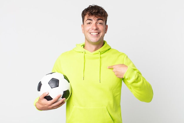 Young handsome man feeling happy and pointing to self with an excited and holding a soccer ball
