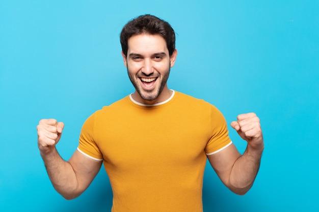 Молодой красивый мужчина чувствует себя счастливым, позитивным и успешным, празднует победу, достижения или удачу
