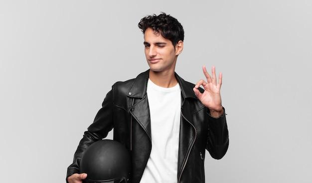 幸せ、リラックス、満足を感じ、大丈夫なジェスチャーで承認を示し、笑顔で若いハンサムな男。バイクライダーのコンセプト
