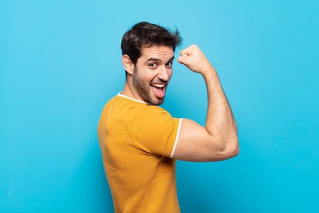 幸せ、満足、パワフル、屈曲フィットと筋肉の上腕二頭筋を感じ、ジムの後に強く見える若いハンサムな男
