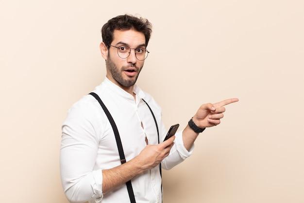 젊고 잘생긴 남자는 행복하고 충격을 받고 놀라며 손으로 입을 가리고 측면 복사 공간을 가리키고 있습니다.