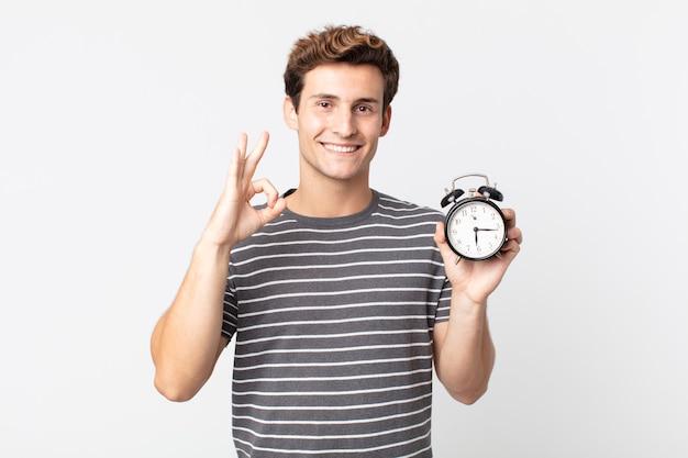 Молодой красавец чувствует себя счастливым, показывает одобрение жестом и держит будильник