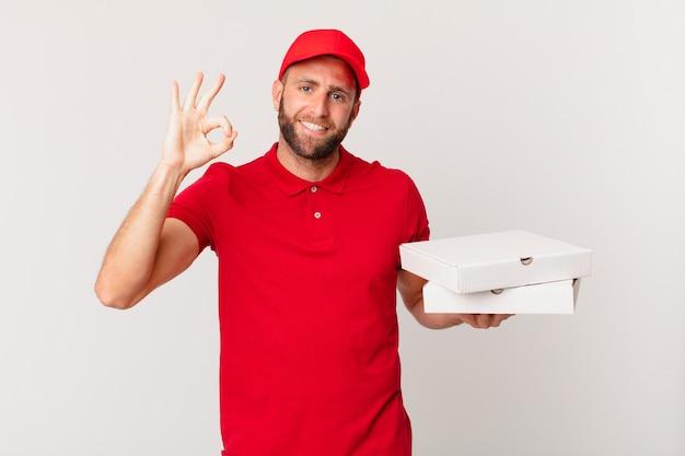 幸せな若いハンサムな男は、大丈夫なジェスチャーで承認を示しています。ピザ配達のコンセプト