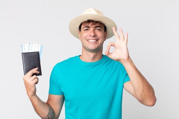 젊고 잘생긴 남자는 행복감을 느끼며 괜찮은 제스처로 승인을 보여줍니다. 여권을 들고 있는 여행자