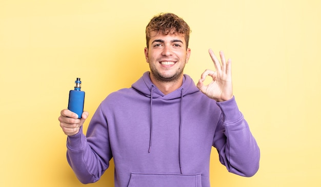 Young handsome man feeling happy, showing approval with okay gesture. vaporizer concept
